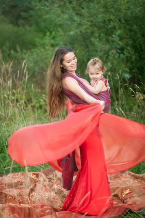 Beautiful woman in a red costume for belly dancing with her daughter in a baby sling