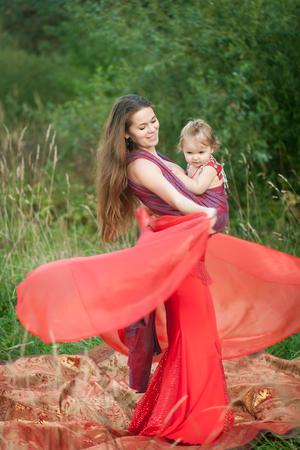 Hermosa mujer vestida con un traje rojo para la danza del vientre con su hija en un portabebés