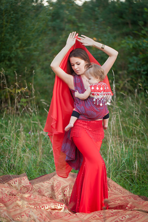 Beautiful woman in a red costume for belly dancing with her daughter in a baby sling Banque d'images - 105927582