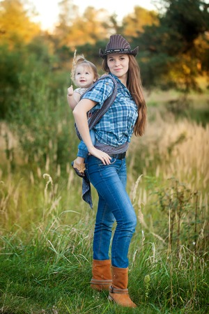 A beautiful cowgirl mother carrying her cute small daughter in a baby sling in the autumn evening. Mom and daughter having fun together Foto de archivo