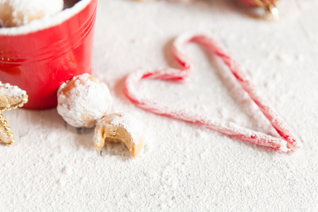 Christmas snowballs cookie balls with powdered sugar. Bright red and white festive decor with stripy candy canes in a heart shape. Christmas food concept Stock Photo