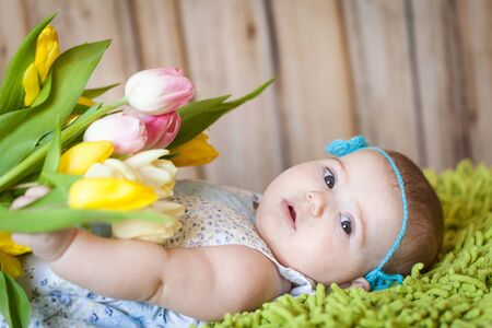 Adorable baby girl with tulips lying on a green blanket. Happy motthers day or spring concept 写真素材