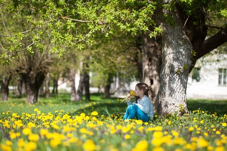 Cute little girl sitting under the tree on a dandelion meadow. Spring relax concept