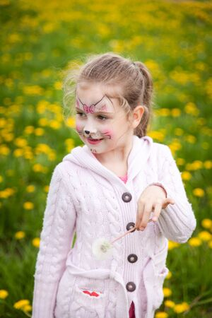 Beautiful young girl with face painting like a kitten enjoys summer time in a dandelion meadow