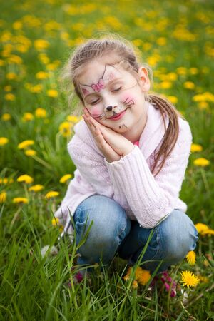 Beautiful young girl with face painting like a kitten dreaming in a dandelion meadow Stockfoto