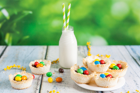 Springtime coconut bird nests filled with Easter eggs on a wooden background
