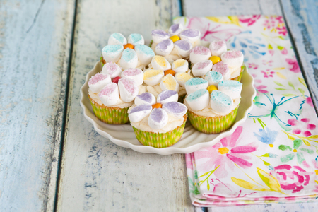 Tasty cupcakes decorated with butter cream and marshmallow flowers on a light wooden background with a floral napkin. Mother's day desserts. Spring or Easter concept