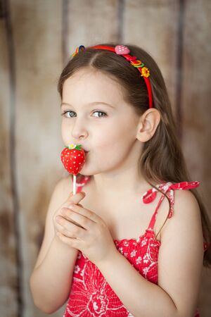 Smiling young girl in a red dress on wooden background eating sweet strawberry cake pops