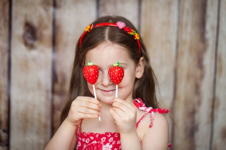 Smiling young girl in a red dress on wooden background hides her eyes with sweet strawberry cake pops