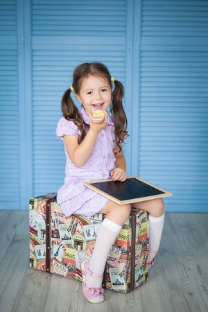 Happy preschool girl with big gingerbread pencil sitting on an old suitcase. Back to school Standard-Bild