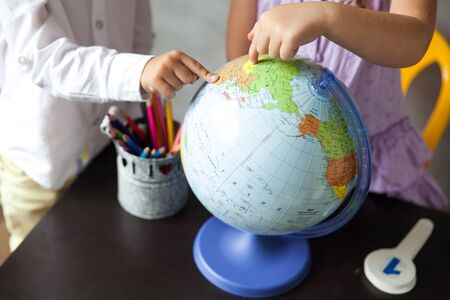 Pre-School children looking at the globe. Back to school concept