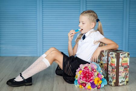Happy school girl with big gingerbread pencil sitting on an old suitcase. Back to school