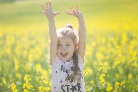 Cute girl having fun in the field of flowering rape. Nature blooms rape seed field. Summer holidays