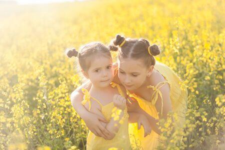 Cute girls in yellow dresses having fun in the field of flowering rape. Nature blooms rape seed field. Summer holidays