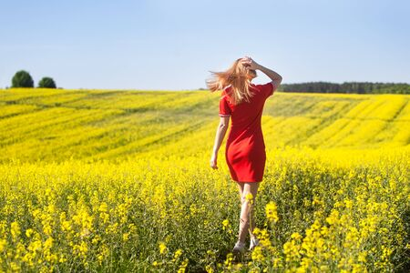 Happy young woman in a red dress enjoying summer in the rape field