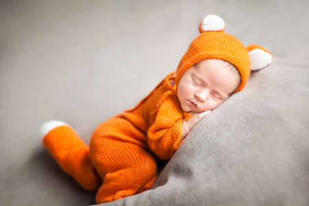 Sleeping newborn baby in cute fox outfit. Fall halloween thanksgiving card