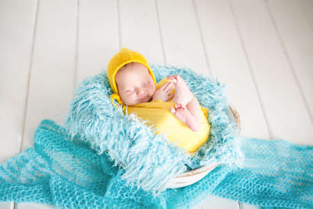 Cute newborn baby girl in yellow bonnet and wrap sleeping in a wooden basket on blue fur. Healthy child, concept of childcare and happy motherhood, happy childbirth