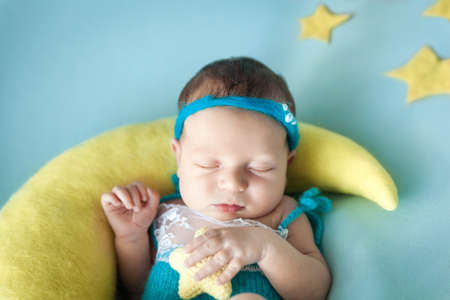 Cute newborn baby girl with a knitted star toy in her hands sleeping on a moon pillow. Healthy child, concept of childcare and happy motherhood, happy childbirth