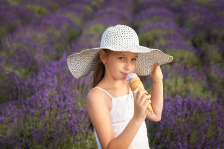 Cute girl in a white dress eating lavender ice-cream in a lavender field