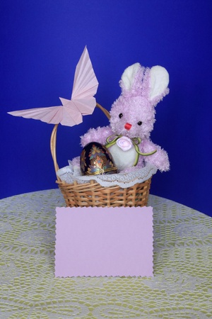 blue egg: Easter Card - Bunny with Chocolate Eggs  in a Holiday Basket on Blue Background Stock Photo