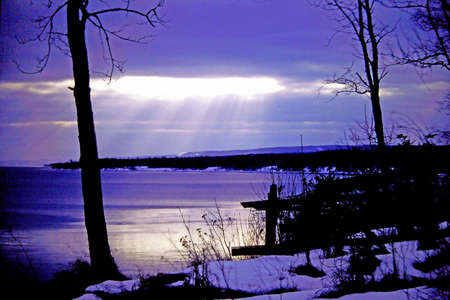 Cold sunstreming through clouds onto a bay of Lake Superior in winter.