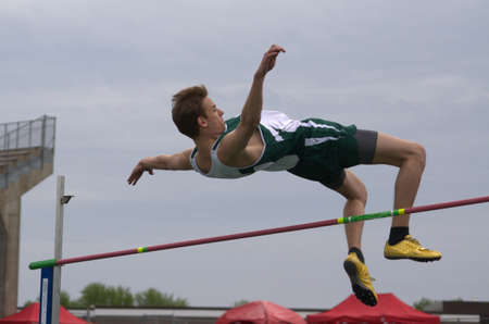 High jumper clearing the bar in a highschool trAntique ack meet