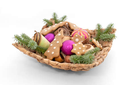 christmas motif: Basket with Christmas decoration and gingerbread on white background Stock Photo