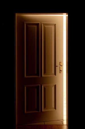 room door: Partly ge�ffnete door in a dark room by a ray of light falls. Stock Photo