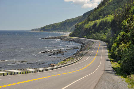 Highway 132 at the coast of Saint Lawrence River in Quebec, Canada. The route is part of the Gaspa ? Peninsula (Gaspa ? them), a northward continuation of the Appalachian Mountains called the Chic-Chocs