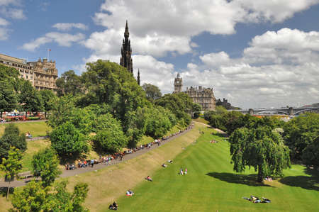 scott monument: Edingburgh, Scotland - July 7, 2010: East Princess Street Gardens in EdinburghScotland with view to the Scott Monument, the Balmoral Hotel and the North Bridge. In the park people are relaxing in the sun.
