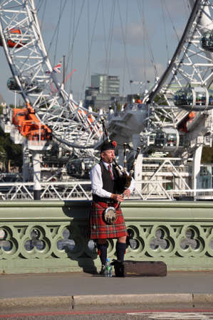 bagpipe: London, Great Britain - October 10, 2012: Bagpipe player on Westminster Bridge in front if the London Eye
