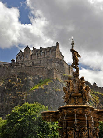 sommer: Edinburgh Castle behind a curtain of waterdrops by a golden fountain in summer