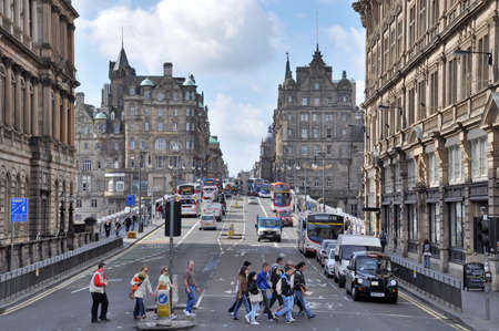 public transfer: Edinburgh, Great Britain - July 7, 2010: View towards North bridge and the Old Town of Edinburgh with heavy traffic, busses and people crossing the street. Editorial
