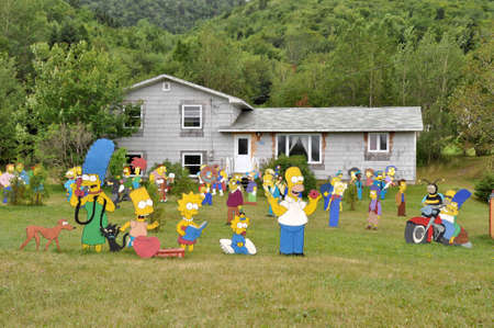 cardboard cut-outs of the Simpsons charakters in a private garden near Baddeck on Cape Breton Island, Canada