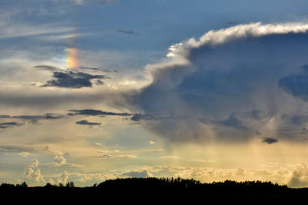 thundercloud: Parhelion (sundog) next to a thundercloud, atmospheric phenomenon created by light interacting with ice crystals Stock Photo