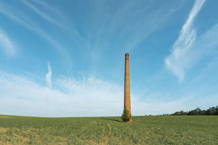 abandoned historic free standing chimney in a field