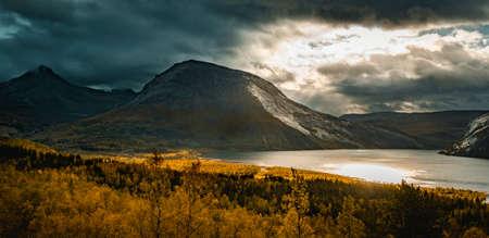 Kobbvatnet (also known as (Njuorjojávri) lake with the summits of Kviturdtinden (center) and Gjerdalstinden, in background at dramatic autumn light.
