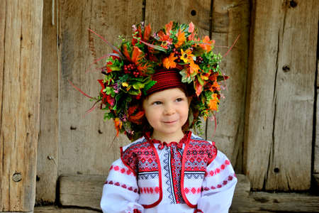 ethnographic: a girl of three years in the national Ukrainian clothes in a wreath of flowers, leaves and berries on the porch of an authentic Ukrainian house. ethnographic festival, summer, Ukraine Stock Photo