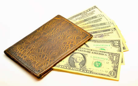 2 5: old, worn leather wallet with dollars lying underneath banknotes of 1, 2, 5, 20 and 100.