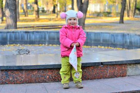 late fall: cheerful little girl in a funny hat and a pink jacket with a handkerchief in his hands in a city park. late fall.