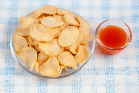 pretzel stick: Grissini sticks, potato chips and other salty snacks with chili sauce