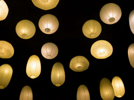 warmly: Many warmly colored balloon paper lamps isolated on black background Stock Photo