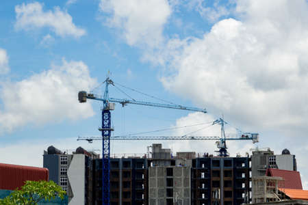 realestate: Crane and building construction site against blue sky