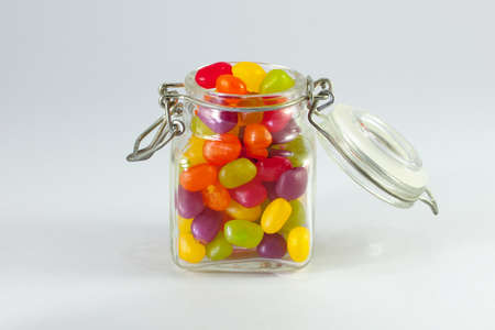 Jelly Beans spilt from Glass Jar with Open Lid and Metal Clasp II Stock Photo