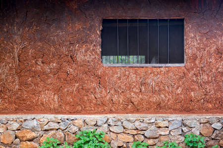 Wall of a house in red clay, earth , great texture background, poverty, developing or tropical country concept. Stock Photo