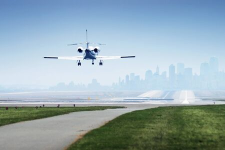 Photo of an airplane just before landing. city in background photo