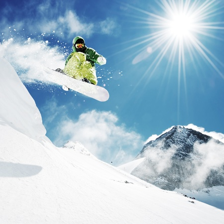 snowboard: Snowboarder at jump inhigh mountains at sunny day.