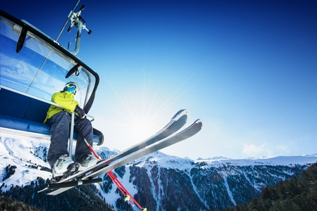 Skier siting on ski-lift - lift at sunny day and mountain Banque d'images