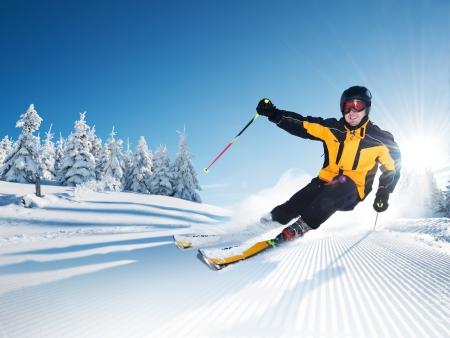 Skiër in de bergen, geprepareerde piste en zonnige dag Stockfoto