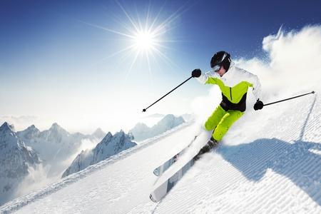 Skiër in bergen, geprepareerde piste en zonnige dag
